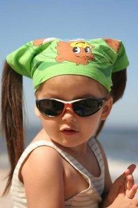 Bimba con occhiali da sole sulla spiaggia
